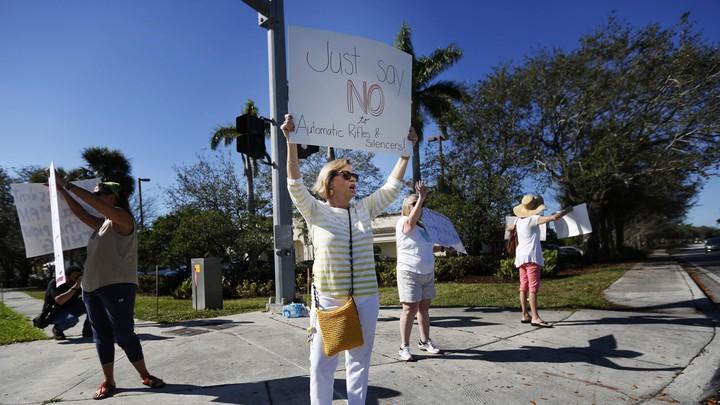 A teacher holds up an anti-gun sign.