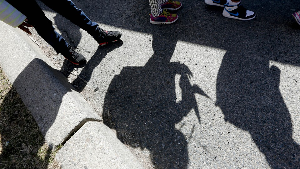 Shadows of students and their sneakers waiting for a school bus