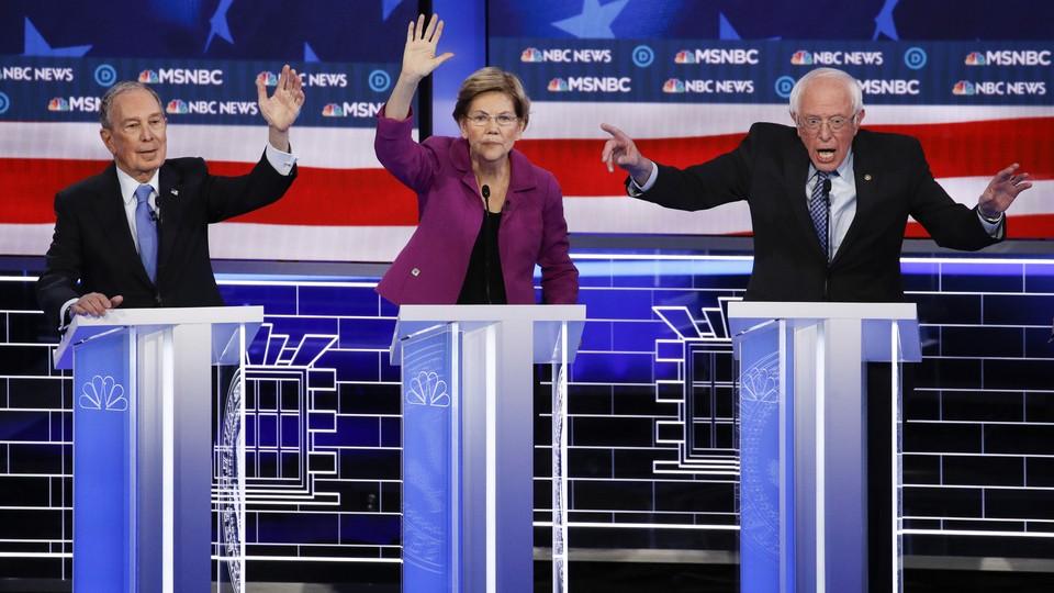 Michael Bloomberg, Elizabeth Warren and Bernie Sanders stand behind lecterns during the Democratic debate.