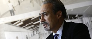 A portrait of architect Phil Freelon sitting in front of a wall covered with design renderings.