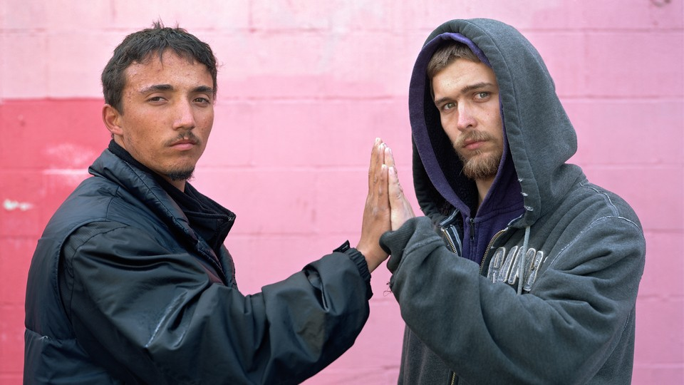 Two strangers touching hands and looking at the camera