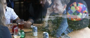 Young women and men chat over beers in a bar.