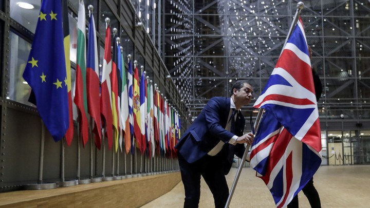 A person removes the British flag from a hall with European flags.