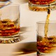 photo of brown liquor being poured over ice into multiple highball glasses