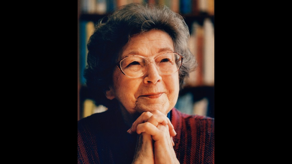 A photo of Beverly Cleary smiling, resting her chin on her clasped hands