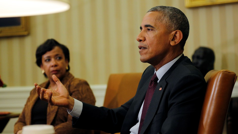 Image shows President Obama seated in a brown leather chair, right hand raised slightly, addressing someone out of the frame. Attorney General Loretta Lynch sits to his right, looking at hiim.