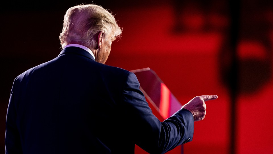 Former President Donald Trump stands with his back to the camera, pointing a finger to the right.