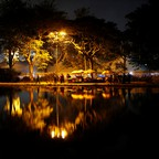 People in the park at night in front of water