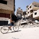 A boy rides on a bicycle in the town of Kafr Batna, in eastern Ghouta, Syria on September 5, 2018.