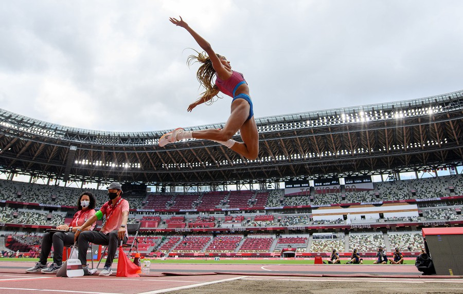 A long jumper is photographed in mid-air above the track.