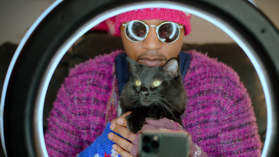 A cat person holding his black cat in front of a ring light