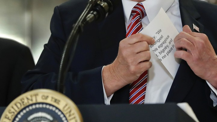 President Trump reaches for a prepared statement in his pocket