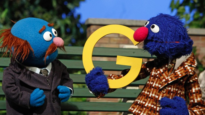 "Grover holds up a yellow ""G"" as Fat Blue looks at him. They sit on a park bench."