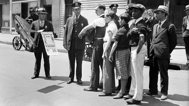 In a black and white photo, health officers at a checkpoint question people in line waiting to be screened to prevent spread of smallpox