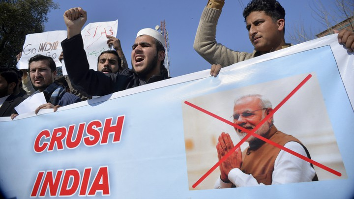Pakistani men attend a rally with a banner that shows Indian Prime Minister Narendra Modi's face crossed out.