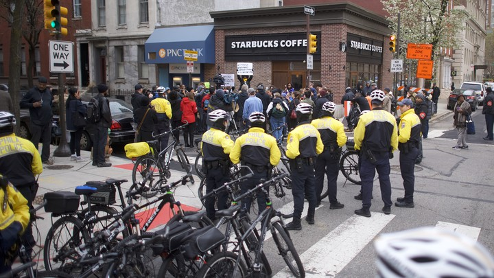 Police stand outside of a Starbucks.