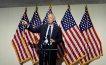 Ron Johnson talks at a press conference in front of American flags.