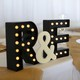 A decoration featuring a couple's initials sits on a table at a wedding reception.