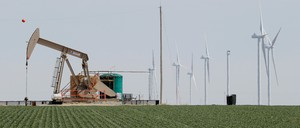 An oil derrick and wind turbines stand next to each other on plains in Texas.
