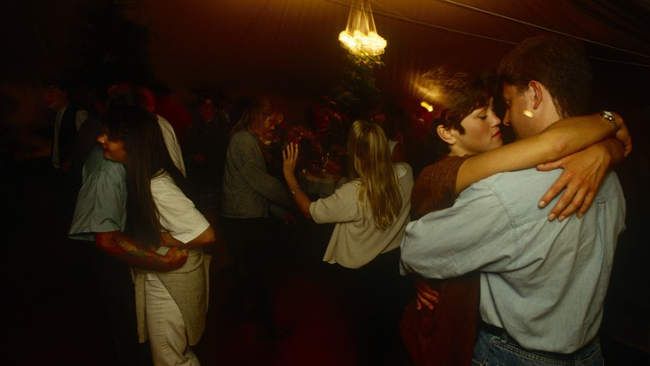 Couples dance closely in a dimly lit room.