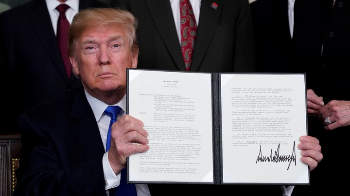 President Trump holds his signed memorandum on intellectual-property tariffs on high-tech goods from China on March 22, 2018.