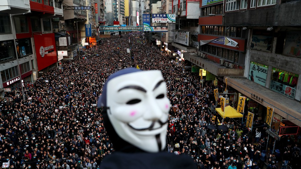 A protester wearing a Guy Fawkes mask heads a demonstration in downtown Hong Kong.