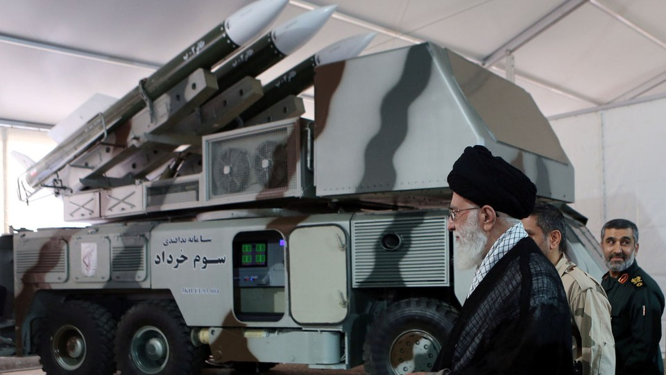 """Ayatollah Ali Khamenei is seen near a """"3 Khordad"""" system, which is said to have been used to shoot down a U.S. military drone."""