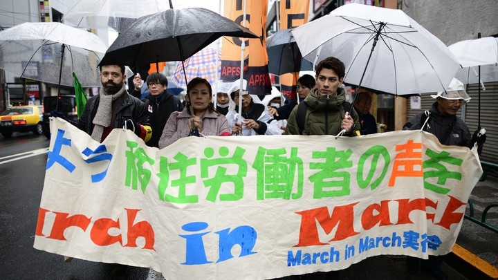 Migrant workers march together on the streets of Tokyo holding banners and umbrellas.