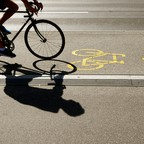 A photo of the silhouette of a cyclist on a bike lane.