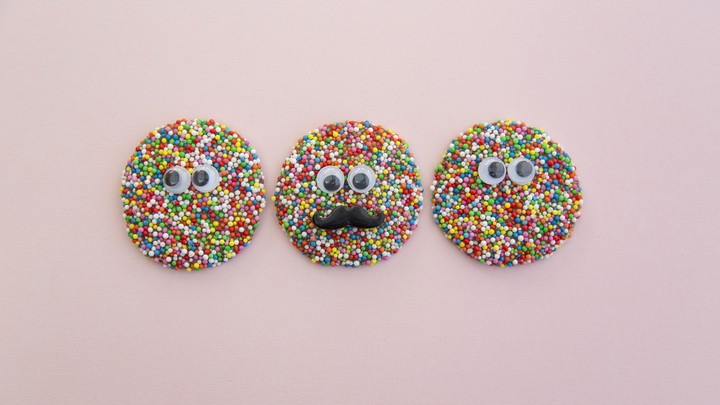 Three sprinkled cookies with plastic googly eyes on them