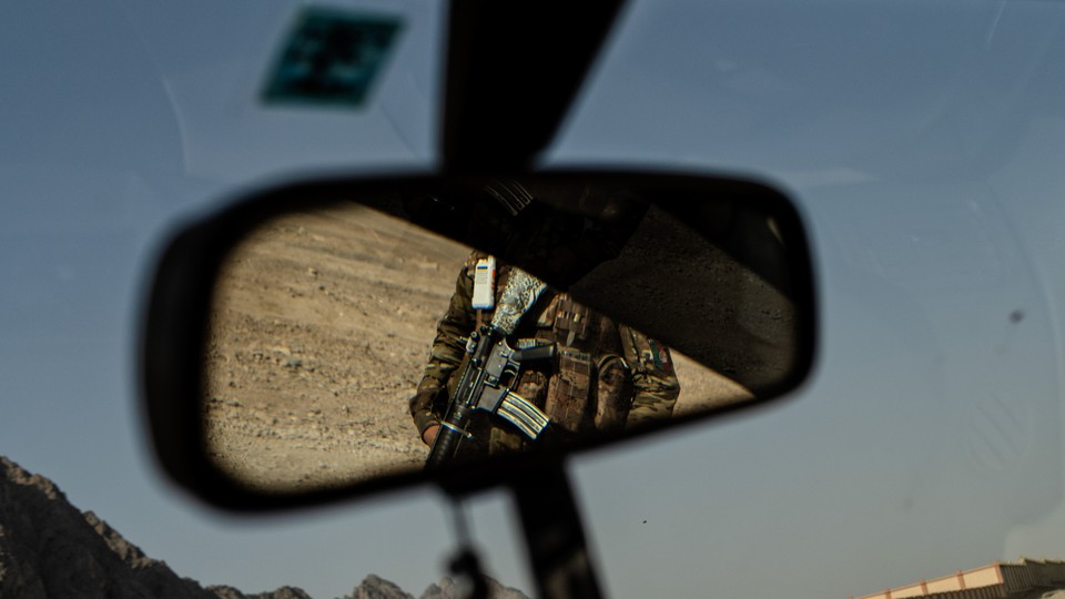 A soldier appears in a rear view mirror