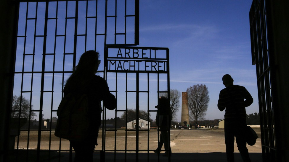 """Visitors enter Sachsenhausen through a gate with the words """"Arbeit macht frei"""" (works sets you free)."""
