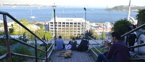 Young people sit on the stairs next to the Roma bostan to take in the view.