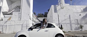 a photo of a young woman in a Fiat 500 car.