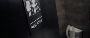 An open door leads to a public bathroom