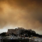 Orange smoke from a wildfire burning outside Athens is seen over the hill of the Acropolis.