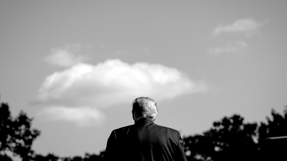 A black and white photograph of Donald Trump at the White House, facing away from the camera.
