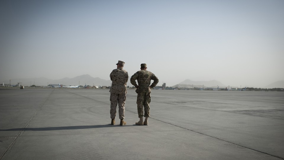 Generals John Allen and David Petraeus stand at an airfield in Afghanistan