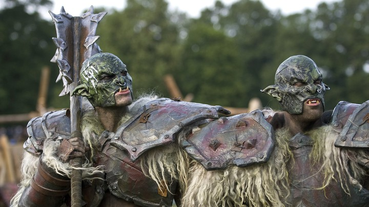 Two tall men in armor and troll costumes stand outside in Germany.