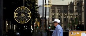 """A man walks past glass windows which say """"Office of the District Attorney"""""""