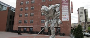 A large sculpture of a hockey player next to the Prudential Center in Newark, where the New Jersey Devils hockey team plays. In the background, signs can be seen for Dinosaur Bar-B-Cue BBQ and Rock Plaza Lofts luxury apartments.