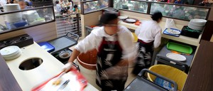 Food court workers sift out scraps at a mall.
