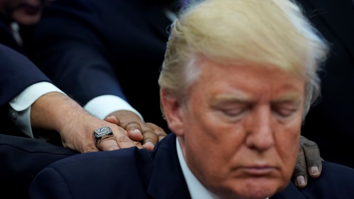 Donald Trump looks down as three men, whose faces are not visible, lay their hands on his back and shoulders.