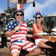 A photo of a man and woman wearing American flag-themed clothing drinking on an outdoor patio