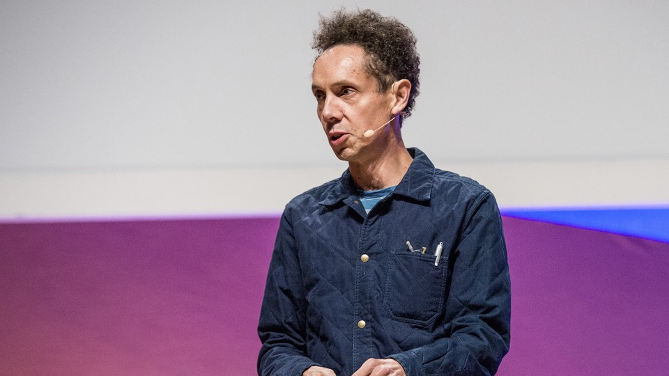 Malcolm Gladwell stands in front of a purple-and-blue screen giving a speech.
