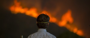 photo: a man watches a wildfire.