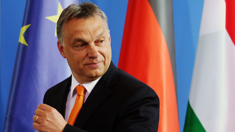 Hungarian Prime Minister Viktor Orbán stands in front of the European Union flag.