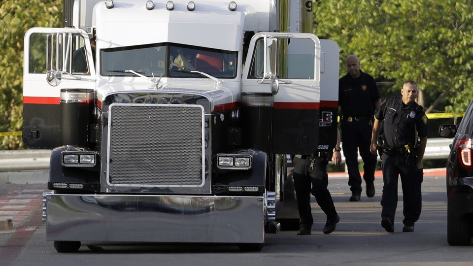 San Antonio police officers investigate the scene where eight people were found dead in a tractor-trailer loaded with at least 30 others outside a Walmart store in stifling summer heat in what police are calling a horrific human trafficking case.