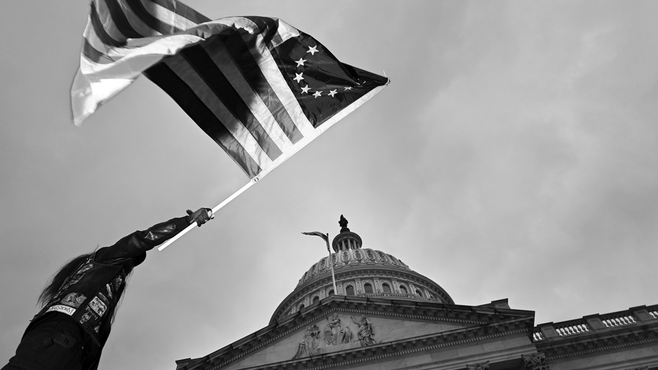 A man waves a flag on the grounds of the U.S. Capitol.