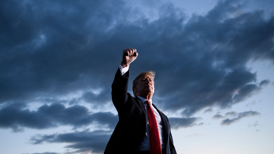 President Trump, standing, raises his fist, with a dark sky behind him